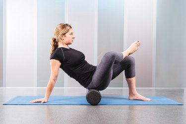 woman using foam roller on an exercise mat