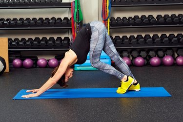 Woman demonstrating how to do Downward Dog pedal stretch