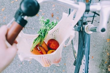 Someone bikes with a bag of veggies.