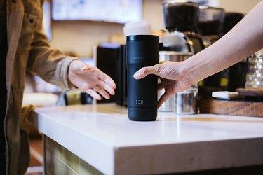 A barista hands an Ember to a customer.