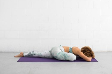 woman does pigeon pose ab exercise on a yoga mat