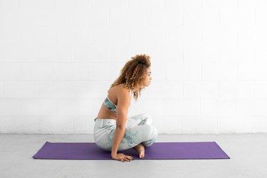 woman does seated hover ab exercise on a yoga mat