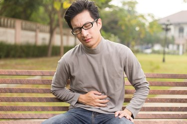 A man holds his stomach in pain.