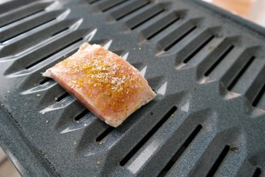 Seasoned salmon filet on a broiler tray ready to be cooked