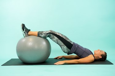 Woman performing Swiss ball glute raise.