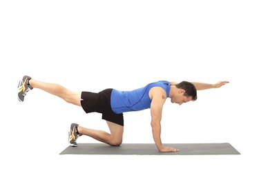 Man doing the bird-dog exercise to work his abs.