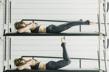Woman performing grasshopper Pilates exercise.
