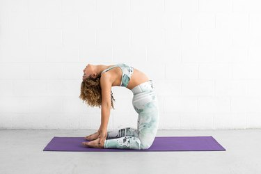 woman does camel pose ab exercise on a yoga mat