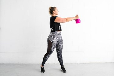 woman doing standing torso twist ab exercise