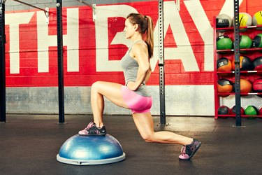 Woman performing front lunge BOSU ball exercise