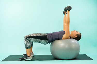 Woman performing Swiss ball chest press.