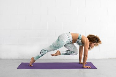 woman does knee pull plank ab exercise on a yoga mat