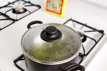 Edamame cooking inside a saucepan on the stove.