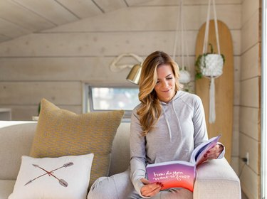 Woman hanging out on couch upstairs or hanging chair upstairs with book