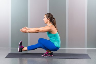 Woman performing single leg squat on mat.