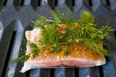 Salmon with fresh herbs on top on a broiler pan in the oven