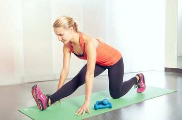 Woman performing a hamstring stretch as part of a HIIT workout