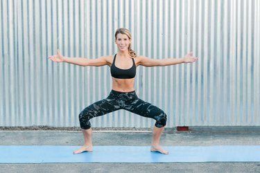 Woman performing plie Pilates exercise