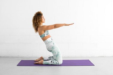 woman does kneeling hinge ab exercise on a yoga mat