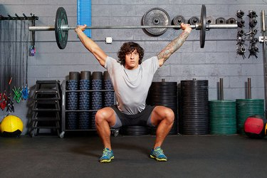 Man performing overhead barbell squat.