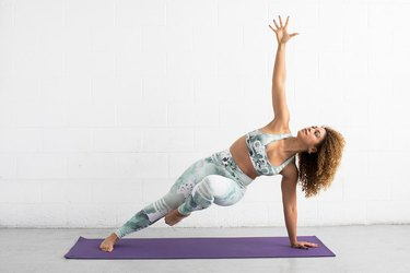 woman does balancing side plank ab exercise on a yoga mat