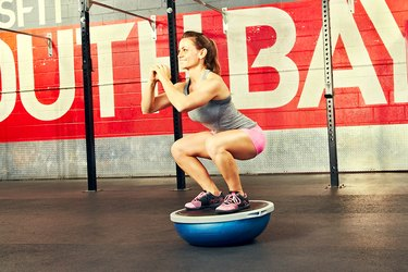 Woman performing BOSU ball exercise squat