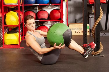 Woman demonstrating how to do Russian twists with a medicine ball in a gym