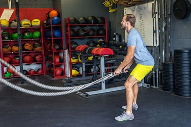 Man demonstrating battle rope exercise for HIIT workout to burn calories