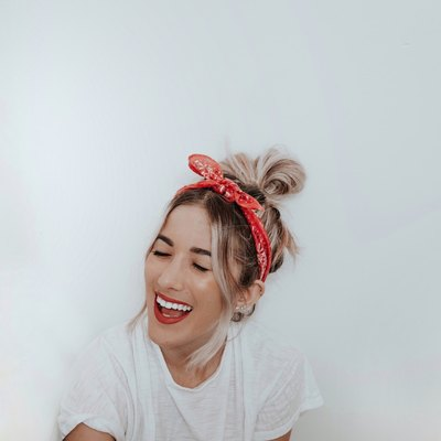 woman smiling in front of white wall