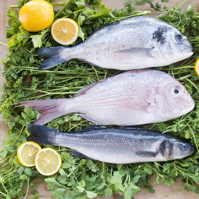 whole fresh fish and lemons on a bed of parsley