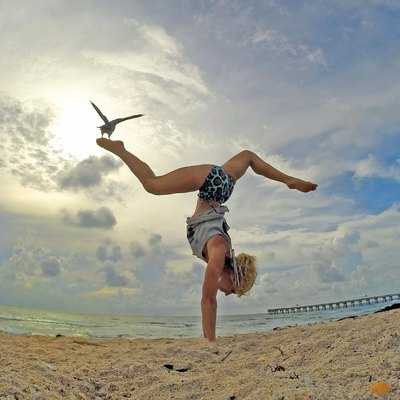 Keri Verna in handstand pose on the beach