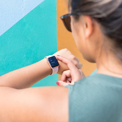 woman checking apple watch to count daily steps 10,000 step challenge
