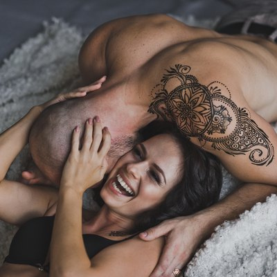 Happy young couple in underwear having fun in bed