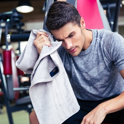 Bodybuilder wipes the sweat at fitness gym