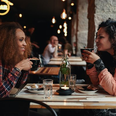 Two women talking and drinking coffee in a cafe