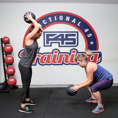 two women working out in an F45 Training Class throwing medicine balls