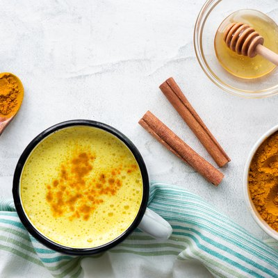 Turmeric latte, cooking golden milk with honey and cinnamon. Concrete background. Top≠
