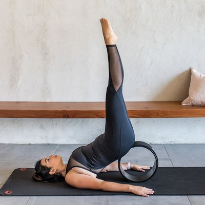 woman doing supported shoulderstand yoga pose on a yoga wheel
