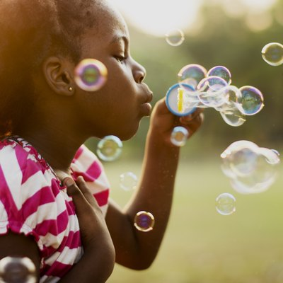 African descent girl playing blowing bubble in a park