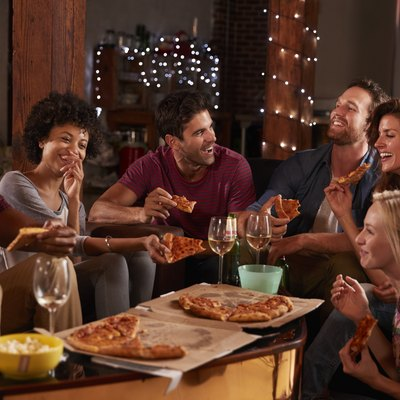 Young adults sharing pizzas at a party at home