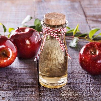 Apple cider vinegar over rustic wooden background