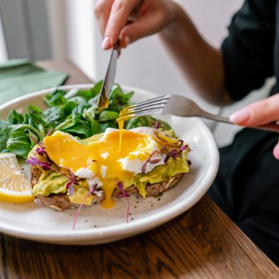 Young woman eat breakfast with knife and fork, Morning in cafe. Healthy breakfast with wholemeal bread toast with avocado, poached egg with green salad
