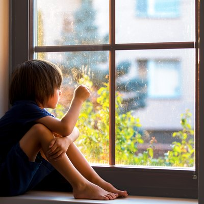 Sad child, boy, sitting on a window ledge