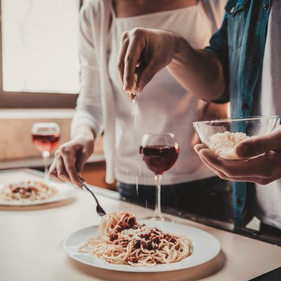 Young couple eating pasta and drinking alcohol, which are some of the foods to avoid with IBS