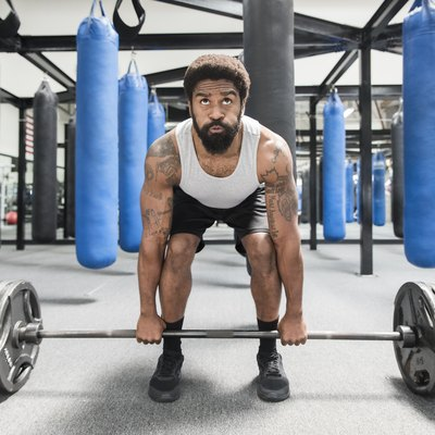 Black man lifting barbell in gymnasium