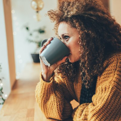 A woman drinking a cup of coffee in a cafe