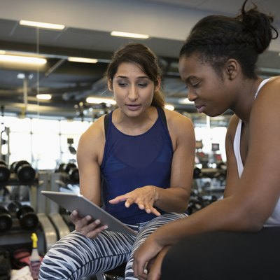 Personal trainer with digital tablet talking with woman in gym
