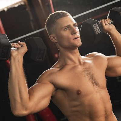 Young handsome bodybuilder doing shoulder press