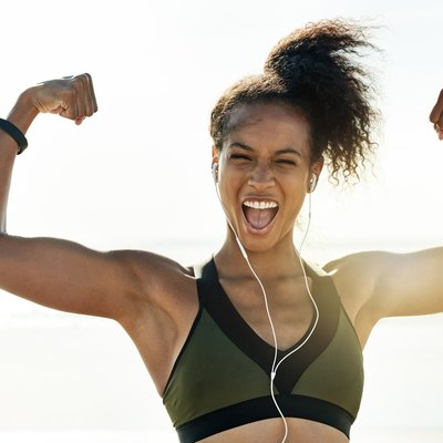 Runner flexing after her training workout on the beach