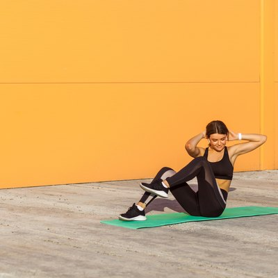 Young sporty woman swing press practicing, doing crisscross exercise, bicycle crunches pose, working out, in sportswear, black pants and top